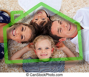 Smiling young family in front of green house illustration -...