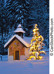 christmas chapel and illuminated tree at evening in bavaria,...