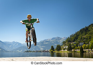 young male teenager jumps high with his dirt bike on a lake...