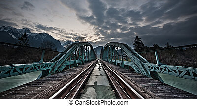 mystical train bridge made of steel and dramatic sky at...