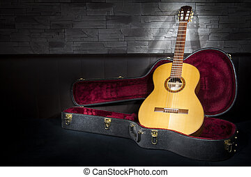 illuminated classic music guitar with case in front of...