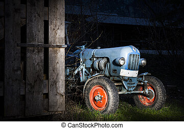 blue oldtimer farming tractor standing next to a wooden hut at night with red painted tires