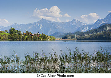 bavarian landscape with lake and fisher boat and tyrolean...