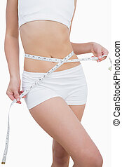 Midsection of slim woman measuring waist over white...