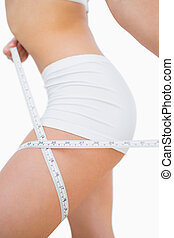 Woman measuring thigh with measuring tape - Midsection of...