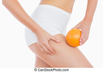 Woman squeezing fat on thigh as she holds orange -...