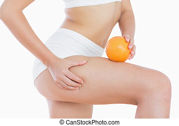 Woman squeezes cellulite skin on thigh as she holds orange -...