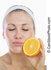 Young woman with eyes closed holding orange slice