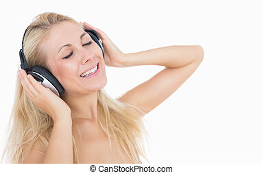 Relaxed woman enjoying music - Relaxed young woman listening...