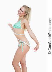 Slim woman measuring waist