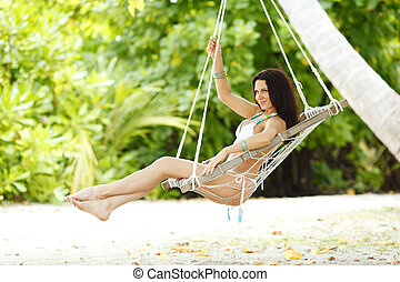 Woman in beach hammock - Beautiful woman swinging in beach...