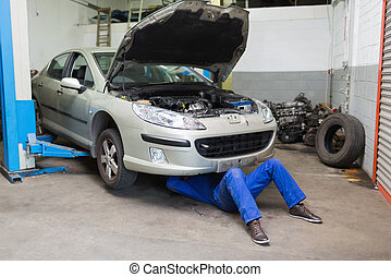 Male mechanic working under car at garage