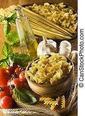 pasta - raw pasta in a bowl with tomato, garlic and basil