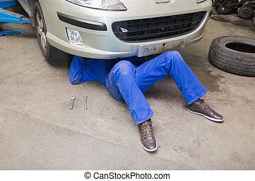 Mechanic working under car in garage