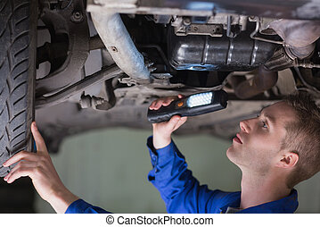 Young mechanic examining car using flashlight