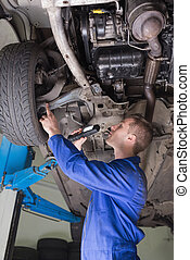 Auto mechanic examining under car - Side view of auto...