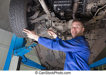 Mechanic repairing car - Young male mechanic repairing car