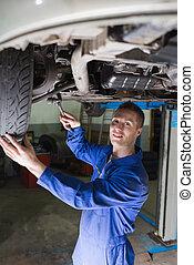 Confident mechanic repairing car