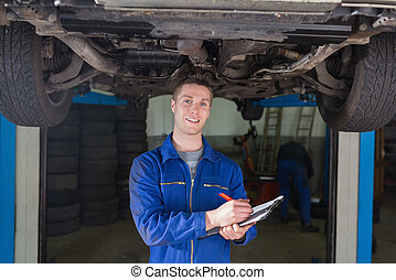Mechanic preparing checklist under car - Portrait of male...