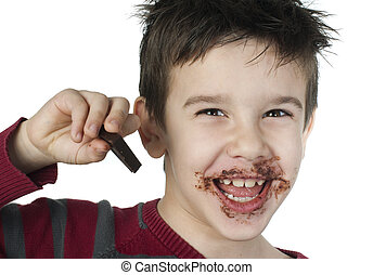 Smiling little boy eating chocolate - Smiling kid eating...
