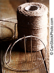 Spool of thread and needle over wooden surface - Artistic...