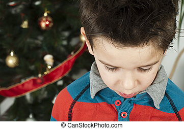 Unhappy little boy on christmass. Christmas tree in the...