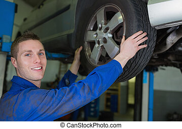 Male mechanic working on wheel of car