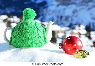 Tea pot in the cap against alpine scenery