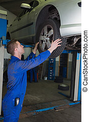 Male mechanic examining car tire - Side view of male...