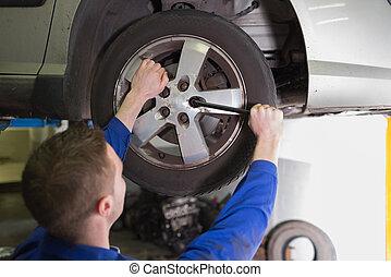Mechanic fixing car tire - Rear view of male mechanic fixing...