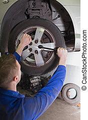 Mechanic fixing car wheel - Male mechanic fixing car wheel...