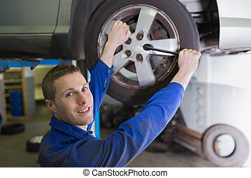 Male mechanic changing car tire - Portrait of confident male...