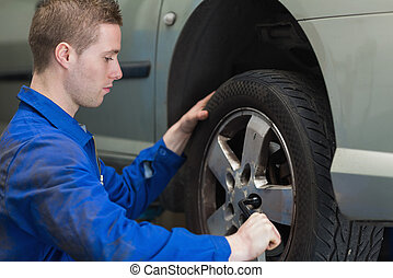 Male mechanic changing car wheel with lug wrench