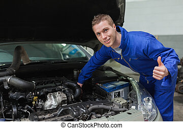 Mechanic under car bonnet gesturing thumbs up - Portrait of...