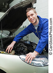 Mechanic closing lid of washer tank - Portrait of male...