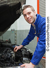 Auto mechanic checking car engine oil - Portrait of male...