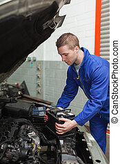 Mechanic checking car battery - Male mechanic checking car...