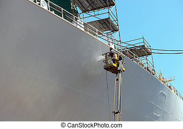 Worker painting of the ship - Worker painting ship hull...