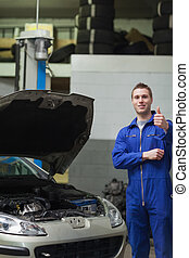 Mechanic by car gesturing thumbs up - Portrait of male...