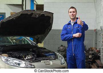 Mechanic by car giving thumbs up gesture - Portrait of male...
