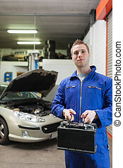 Confident auto mechanic with car battery - Portrait of...
