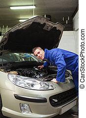 Auto mechanic examining car engine