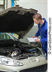Mechanic checking car engine - Male mechanic with clipboard...