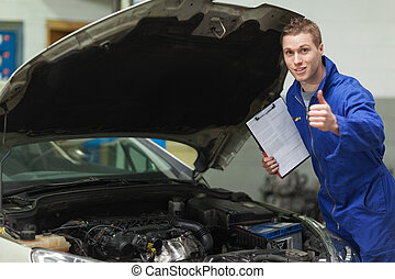 Mechanic with clipboard gesturing thumbs up - Portrait of...