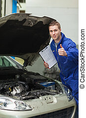 Mechanic by car showing thumbs up - Portrait of male...