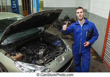 Car mechanic gesturing thumbs up - Portrait of male mechanic...