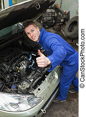 Auto mechanic showing thumbs up sign - Portrait of auto...