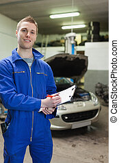Happy auto mechanic writing on clipboard - Portrait of...