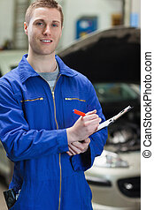 Mechanic writing on clipboard - Portrait of male mechanic...