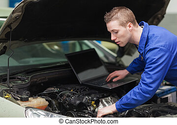 Car mechanic with laptop repairing engine